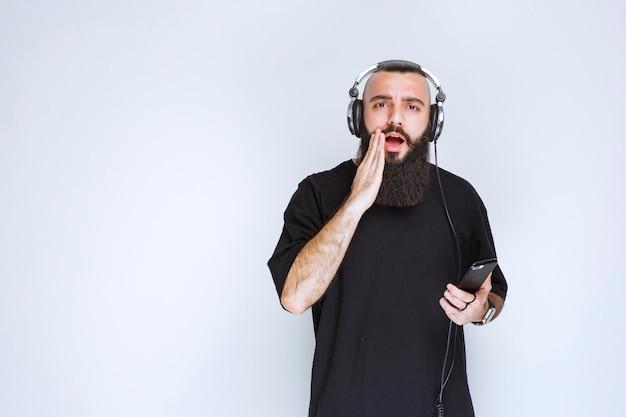 Dj com barba usando fones de ouvido fica surpreso com a playlist.