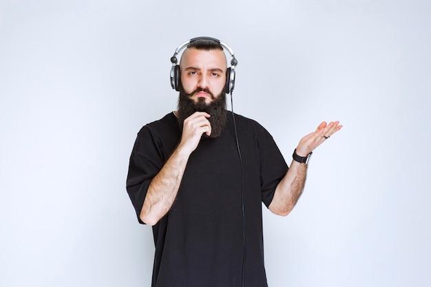 Dj com barba usando fones de ouvido, mostrando o lado direito e fica surpreso.