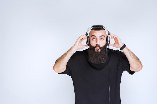 Dj com barba usando ou tirando os fones de ouvido.