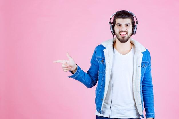 Dj com fones de ouvido apontando para algum lugar