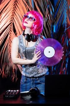 Dj com fones de ouvido, cabelo rosa e discos de vinil rosa