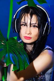 Dj com fones de ouvido com folhas tropicais verdes de monstera
