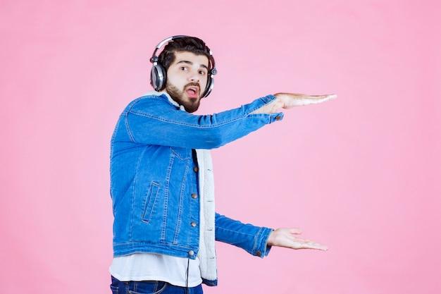 Dj com fones de ouvido mostrando a medida de um objeto