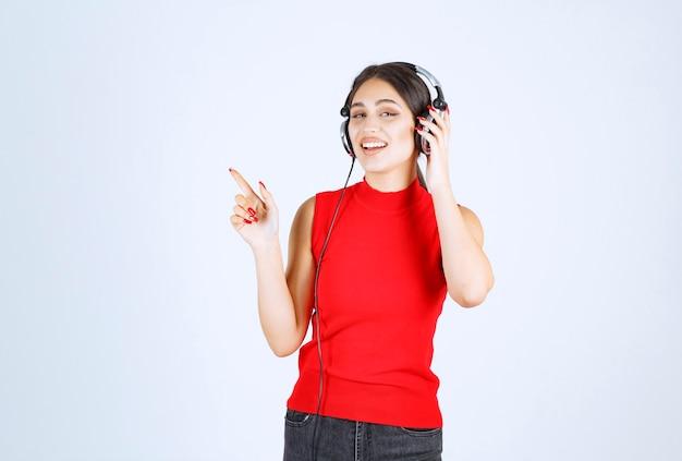 Dj garota com fones de ouvido apontando para ele.