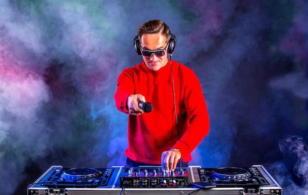 Dj glamoroso com microfone tocando no toca-discos na boate. clube, vida noturna.