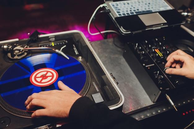 Dj mãos no convés do equipamento e mixer com disco de vinil na festa.