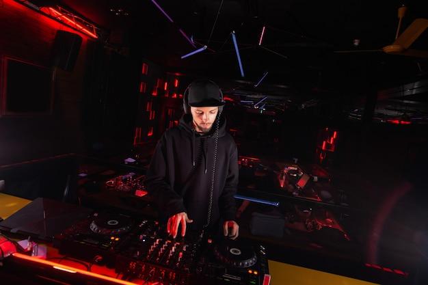 Dj masculino com fones de ouvido, mixando música. melhores faixas. jovem disc jockey concentrado usando toca-discos. boate. luzes azuis e vermelhas do palco no fundo.