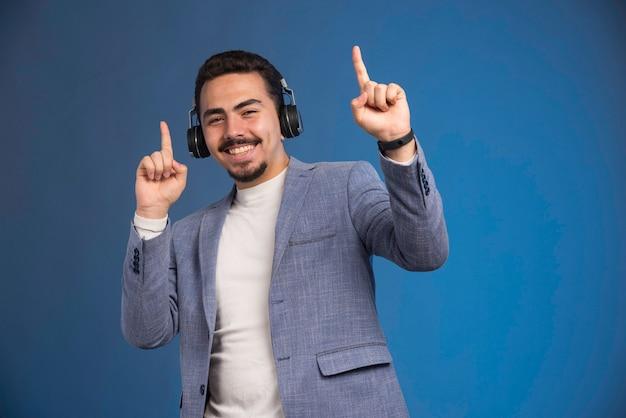 Dj masculino em terno cinza usando fones de ouvido e faz a festa.