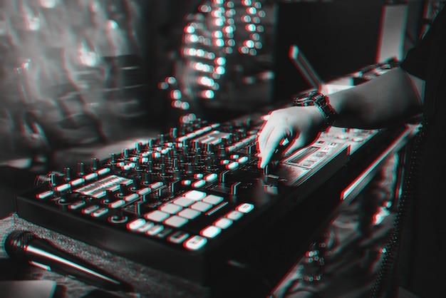 Dj masculino mistura música eletrônica em um controlador de música profissional em uma boate em uma festa.