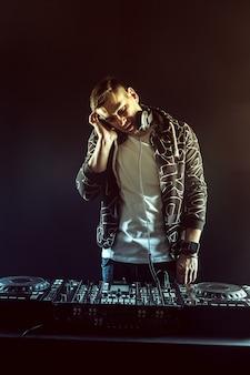 Dj mistura de música na mesa de mixagem em fundo escuro