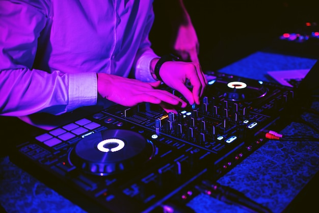 Dj mistura música eletrônica com as mãos em um controlador de música