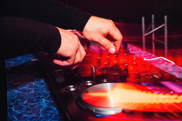 Dj mistura música em equipamento de música profissional com efeitos vermelhos coloridos