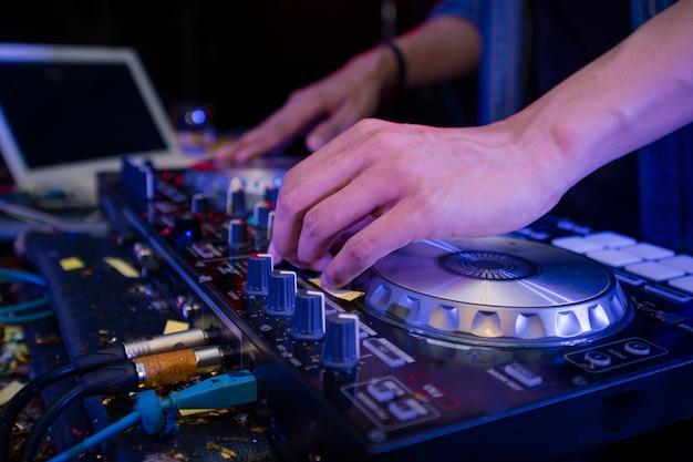 Dj no palco mistura, disc jockey e mix faixas no controlador de mixer de som, tocando música na festa do clube de noite.