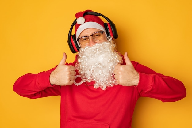 Dj papai noel em fones de ouvido. canções e músicas de natal. fundo amarelo.