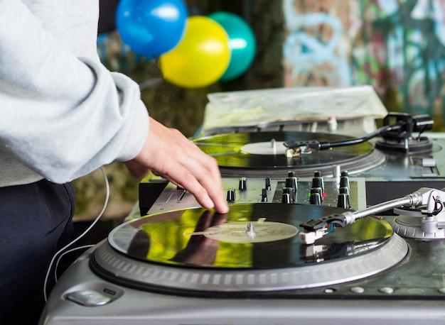 Dj tocando música em uma festa de hip hop. toca-discos analógico, dj usa toca-discos e mixer para fazer scratch. Foto Premium