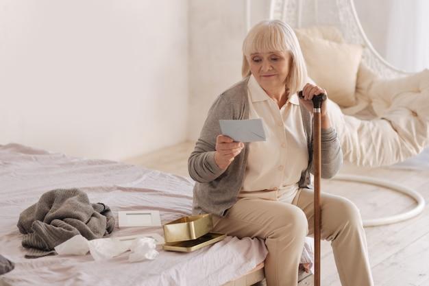 Do meu marido. mulher idosa triste e infeliz sentada na cama segurando uma carta enquanto se lembra do marido