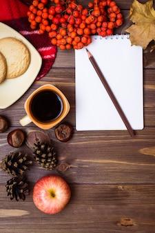 Do outono vida ainda - café, cookies, uma manta, um caderno e um lápis em de madeira.