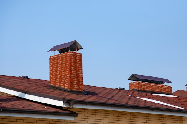 Do telhado da cabana às encostas da chaminé de lampejo no fundo do céu azul do telhado marrom de telhas betuminosas