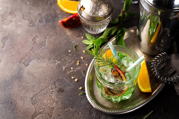 Do tiro acima do cocktail do mojito com gelo e hortelã no vidro com palha.