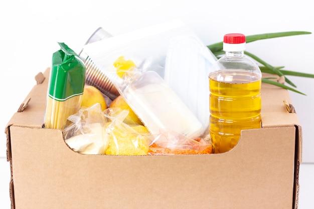 Doação. caixa de supermercado, ajude os produtos a quem precisa. caixa de doação. caixa de papelão com alimentos essenciais sobre uma superfície branca.