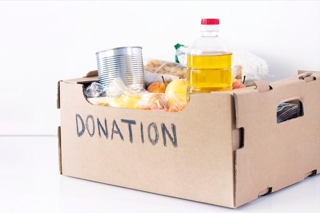Doação. caixa de supermercado, produtos de ajuda para quem precisa. caixa de doação. caixa de papelão com a doação de inscrição com alimentos em uma superfície branca.
