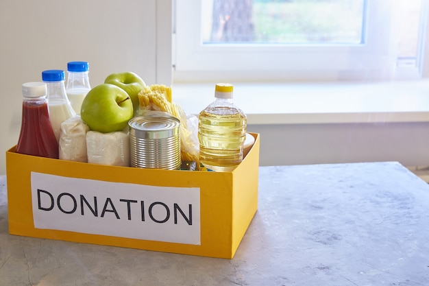 Doação de alimentos em uma caixa em uma mesa perto de uma janela na cozinha em casa. para os pobres e os pobres durante a crise global.