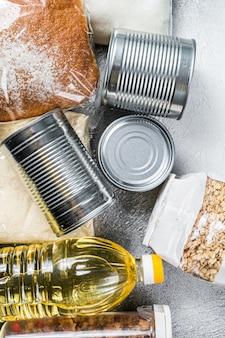 Doação de bens alimentares, conceito de ajuda de quarentena. óleo, comida enlatada, macarrão, pão, açúcar, ovo. fundo branco. vista do topo.