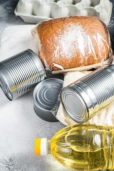 Doação de bens alimentares, conceito de ajuda de quarentena. óleo, comida enlatada, macarrão, pão, açúcar, ovo.