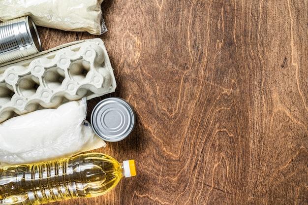 Doação de entrega de comida, conceito de ajuda de quarentena. óleo, comida enlatada, macarrão, pão, açúcar, ovo