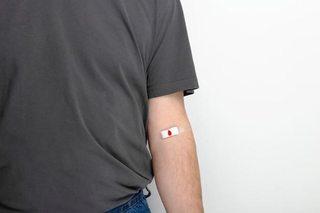 Doação de sangue. homem na mão de camiseta cinza gravada com remendo com gota vermelha depois de dar sangue no fundo cinza.