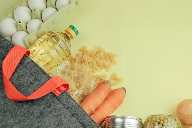 Doações de alimentos em bolsa de linho. entrega de comida em um saco ecológico, comida enlatada, macarrão, ervilhas, biscoitos, ovos, manteiga.