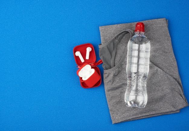 Dobrada cinza esportes feminino camiseta e garrafa de água sobre um fundo azul