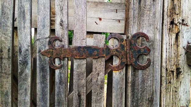 Dobradiça enferrujada em um portão de madeira