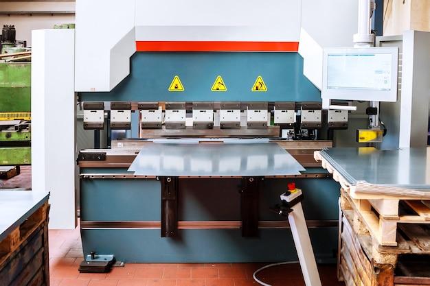 Dobrando chapas de metal com uma máquina de dobra hidráulica na fábrica.