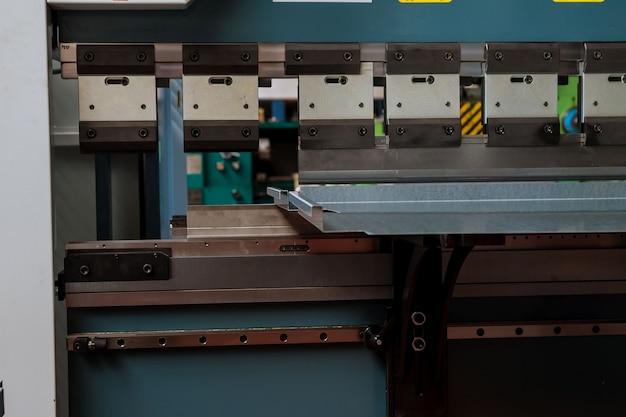 Dobrando chapas de metal com uma máquina hidráulica na fábrica