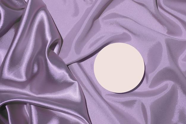 Dobras de tecido de cetim lilás e pedestal de pódio para visão superior de cosméticos ou perfumes
