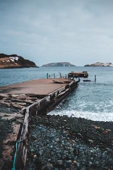 Doca de madeira marrom no mar durante o dia