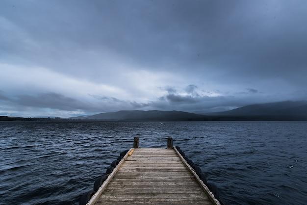 Doca de madeira no lago com a chover na montanha
