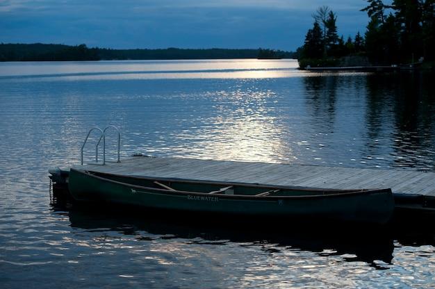 Doca e crepúsculo céu no lago dos bosques, ontário