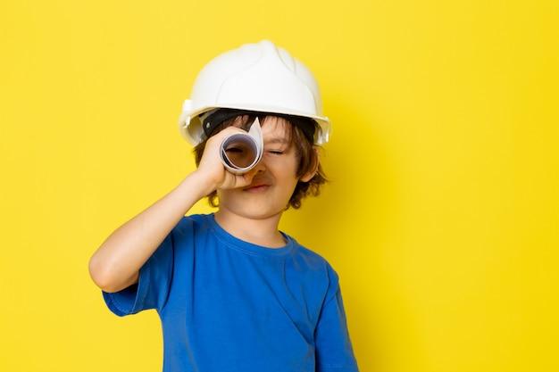 Doce adorável menino bonitinho na camiseta azul, segurando o papel na parede amarela