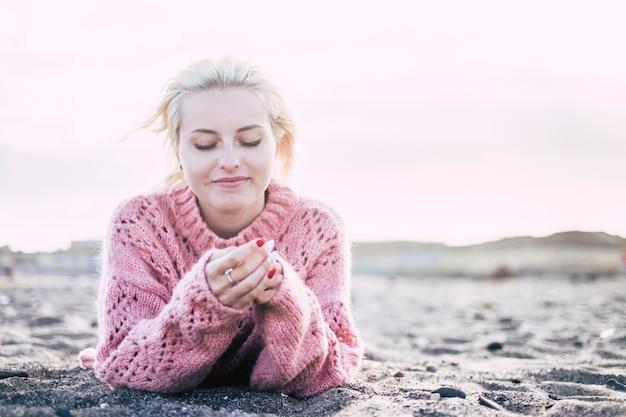 Doce atraente alegre e pensativa jovem loira deitou-se na praia na areia para desfrutar da liberdade e da atividade de relaxamento de lazer. ao ar livre com montanhas