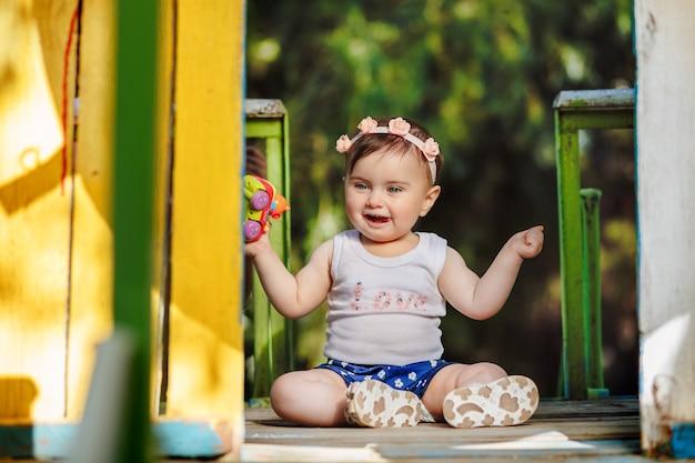 Doce bebê de oito meses rindo no parquinho e segurando seu brinquedo