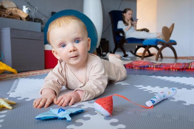 Doce bebê de olhos azuis brincando no chão entre brinquedos