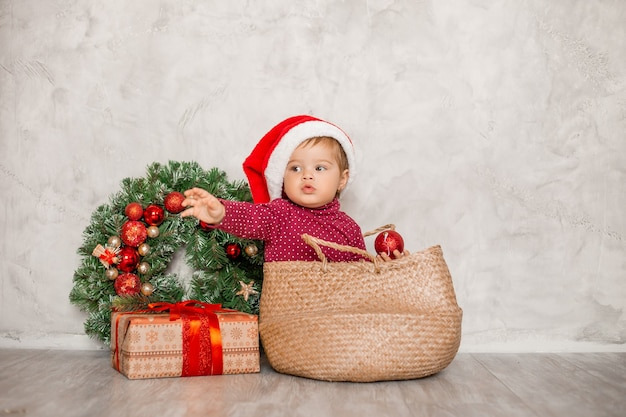 Doce bebê papai noel sentado em uma cesta de vime com uma caixa de presente