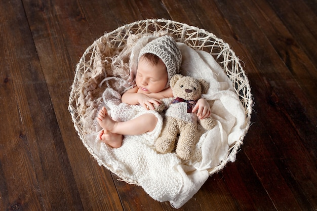 Doce bebê recém-nascido dorme com um brinquedo na cesta.