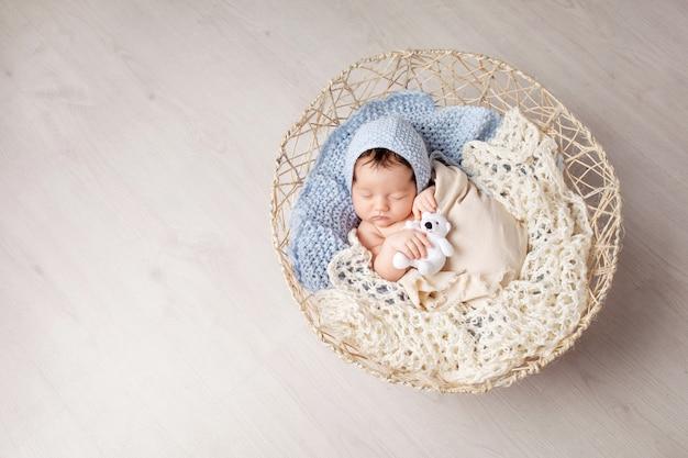 Doce bebê recém-nascido dorme em uma cesta. lindo menino recém-nascido com brinquedo de urso. copie o espaço