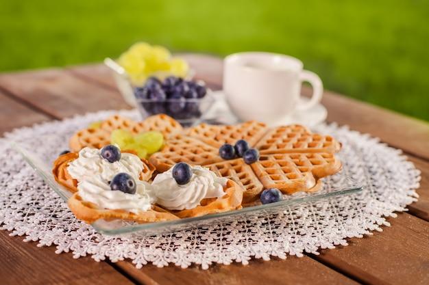 Doce café da manhã na mesa de madeira no jardim