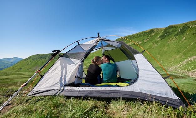 Doce casal beijando na tenda em umas férias ativas de verão nas montanhas. as montanhas estão cobertas de vegetação sob um céu azul claro. perto da barraca estão bastões de trekking