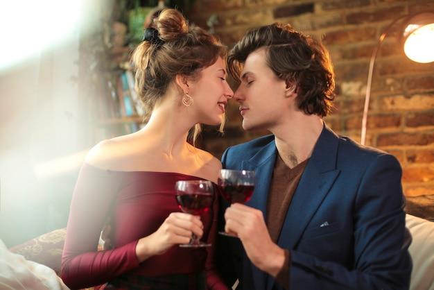 Doce casal comemorando com uma taça de vinho tinto, em casa
