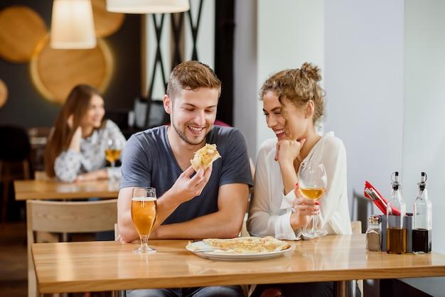 Doce casal comendo pizza e bebendo cerveja e vinho na pizzaria.